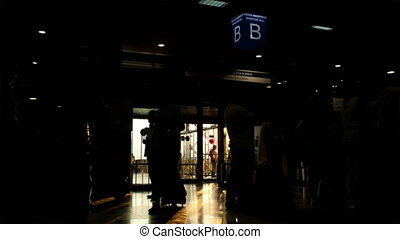 Silhouette of passengers in the airport carrying bags and luggage trolleys in the early morning with back lit sun rays going through the window