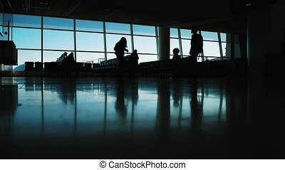 Silhouette of passengers inside the air Airport terminal -...