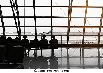 silhouette of passengers waiting for the airplane in the airport