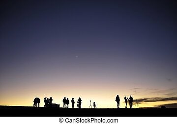 Silhouettes of people against the night sky