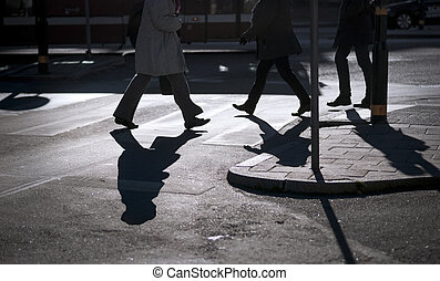 Silhouette of people crossing at pedestrian crossing