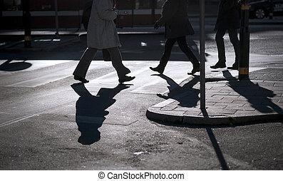 Silhouette of people crossing at pedestrian crossing
