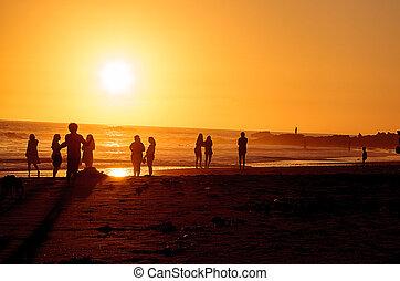 Silhouette of people enjoying the beach