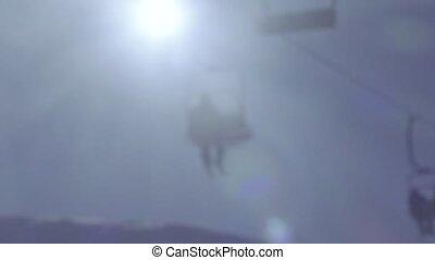 Silhouette of people on ski lift. Bokeh