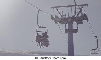 Silhouette of people on ski lift