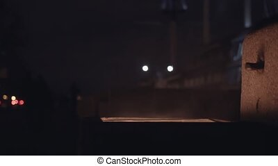 Silhouette of people pass by burning garbage can on the city street at night