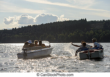 Silhouette of people racing with powerboats