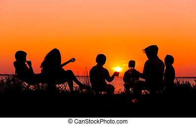 Silhouette of people sitting on the beach with campfire at sunse