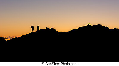 silhouette of people standing on a mountain ridge