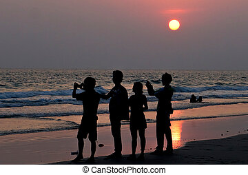 Silhouette of people taking sunset picture on beach