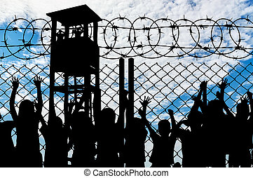 Silhouette of people viewing tower and refugees behind metal bars and barbed wire