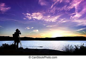 Silhouette of photographer with his equipment during sunset