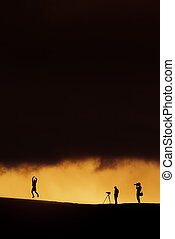 Silhouette of photographers on sunset