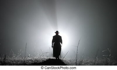 Silhouette of plague doctor man in long mantle costume and hat is walking ahead through smoke to camera. Halloween concept, historical medieval character. High quality 4k footage