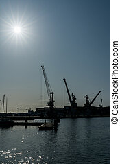 silhouette of port cranes in a large commercial port under a blue sky with a sun star