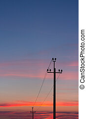 Silhouette of power lines against the background of a bright sunset