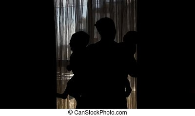 silhouette of pregnant mother six months old baby and...