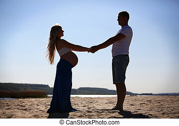 Silhouette of pregnant woman and ma