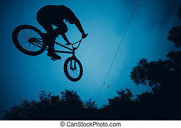 Silhouette of professional young sportsman cyclist with bmx bike jumping at skatepark
