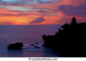 Silhouette of Pura Tanah Lot at coloured sunset. - Old hindu...