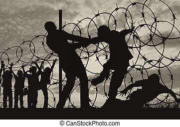 Silhouette of refugees and barbed wire - Concept of...