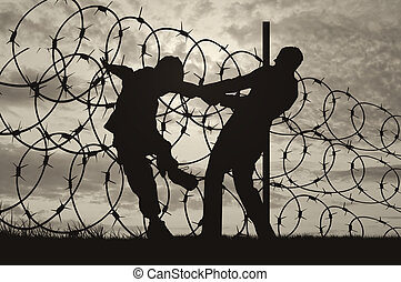 Silhouette of refugees and barbed wire