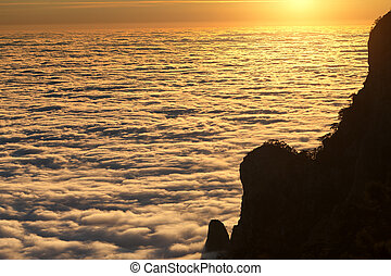 Silhouette of rocks and sea in sunlit clouds at sunset