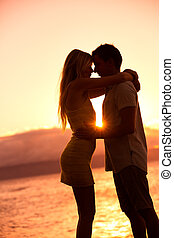 Silhouette of Romantic Couple Kissing at Sunset