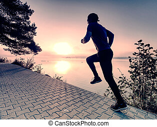 Silhouette of runner man along on the beach at sunset with sun