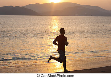 Silhouette of runner on the beach at sunset