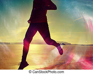 Silhouette of runner person running along on the beach