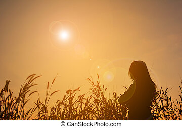 Silhouette of sad women in grass field at the sky sunset
