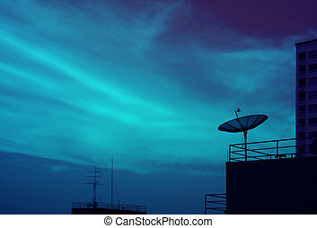 Silhouette of Satellite Dish on the High Building Against Evening Sky in Blue Color Tone