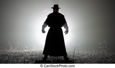 Silhouette of scary plague doctor man in long mantle costume standing in front of bright spotlight. Halloween, horror concept, historical medieval character. High quality 4k footage