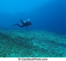 Silhouette of Young Man Scuba Diver between Water Surface and Sea Bottom
