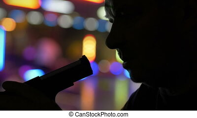 Silhouette Of Serious Male Holding Pistol And Preparing To Kill Himself Suicide