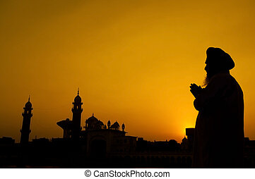 Silhouette of Sikh prayer at temple, Amritsar, India