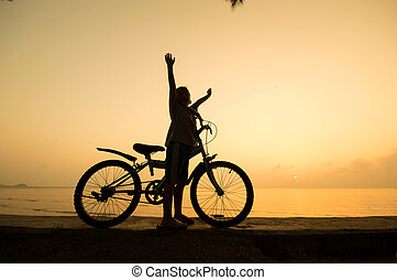 silhouette of small boy with bycycle at the beach.