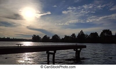 Silhouette of small river pier against evening sun. Wide shot, slow motion