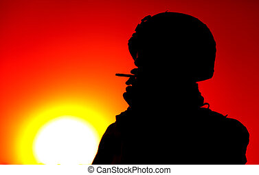Silhouette of smoking on sunset army soldier