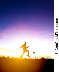 Silhouette of soccer player kicks ball  with sunset background