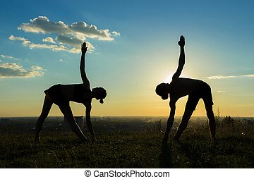 Silhouette of sporty man and woman doing triangle pose