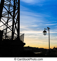 Silhouette of street lamp and the bird at evening time. Porto, Portugal.