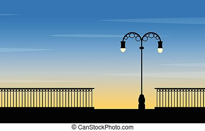 Silhouette of street lamp at sunset landscape