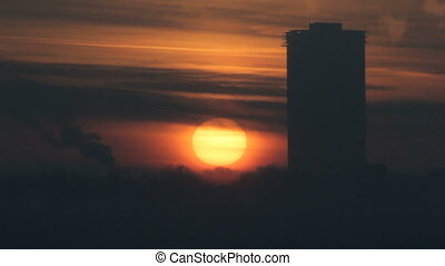 Silhouette of sunset or sunrise in winter city, time-lapse