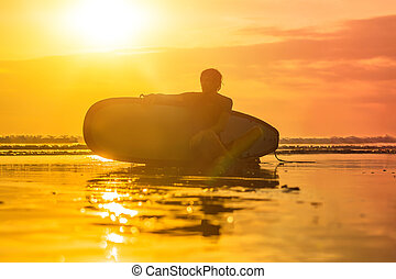 Silhouette of surf man sitting with a surfboard on the seashore beach at sunset time
