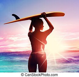 silhouette of surfer with surfboard at sunrise