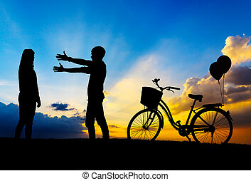 Silhouette of sweet couple in love happy time and bicycle in beautiful sunrise