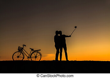 Silhouette of sweet couple in love happy time and bicycle in beautiful sunset