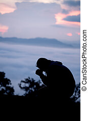 Silhouette of teen girl kneeling and praying over beautiful sunrise background.
